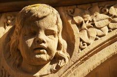 Ein liebevoll entworfener Kopf eines Kindes des verwitterten Sandsteins lizenzfreies stockfoto