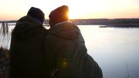Ein liebevolles Paar auf der Flussbank in den Jacken und in den Kappen sitzt auf einem Sonnenunterganghintergrund mit einem Linse stock video