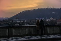 Ein liebevolles Paar, das unter einem Regenschirm mit Blick auf Charles Bridge im Regen bei Sonnenuntergang steht stockbild