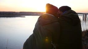 Ein liebevolles Paar in den Jacken und in den Hüten sitzt auf der Flussbank und bewundert den Sonnenuntergang und die Küsse Zeitl stock video