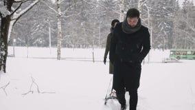 Ein liebevolles Paar geht im Wald mit Schlitten stock video footage