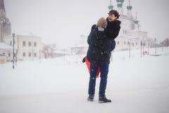 Ein liebevolles Paar geht in Winter auf dem Hintergrund des historischen Anblicks Stockbild