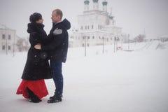 Ein liebevolles Paar geht in Winter auf dem Hintergrund des historischen Anblicks Stockbilder