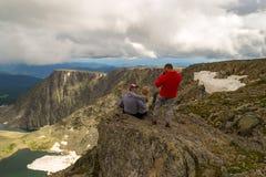 Ein liebevolles Paar stationiert auf dem Berg, der vor Th küsst lizenzfreie stockfotografie