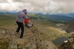 Ein liebevolles Paar stationiert auf dem Berg, der vor Th küsst lizenzfreies stockbild