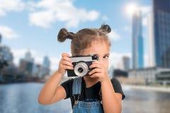 Ein liitle nettes Mädchen, das Foto mit Weinlesekamera macht Lizenzfreies Stockfoto