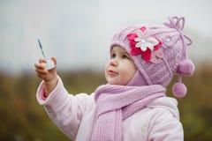 Ein littlegirl brennt Blasen im Herbst durch Stockbilder