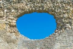 Ein Loch in der Steinwand und im blauen Himmel im Hintergrund, eine ruinierte Wand mit einem Loch lizenzfreie stockbilder