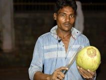 Ein lokaler grüner Kokosnussverkäufer, der eine Kokosnuss aufwirft und schneidet, um das Wasser herauszustellen stockbilder