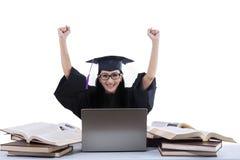 Ein lokalisierter Schuss des erfolgreichen Absolvent mit Büchern und Laptop Lizenzfreie Stockbilder