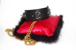 Ein lokalisierter Schuss eines Qualitätslederkragens auf rotem Kissen mit Perlen Stockbild