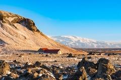 Ein lokalisiertes farmouse sitzt am Fuß eines Berges in Island, lizenzfreies stockbild