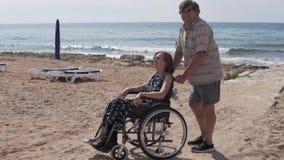 Ein ?lterer Mann tr?gt eine Frau in einem Rollstuhl entlang dem Meer stock video footage