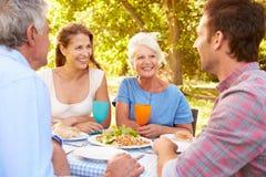 Ein älteres und junges erwachsenes Paar, das zusammen draußen isst Lizenzfreies Stockfoto