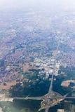 Ein Luftschuß der großen Höhe der flachen Landschaft mit Feldern, Wäldern und Städten Stockfoto