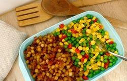 Ein Lunchbox/Plastikein nahrungsmittelbehälter gefüllt mit Gemüsemischung und 'pytt I panna 'der schwedische Name für einen Telle stockbilder