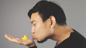 Ein lustiger Kerl, der seine Gummiente küsst lizenzfreies stockbild