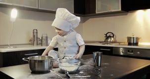 Ein lustiger kleiner Koch sitzt auf einer Tabelle in der Küche und Spielen mit Mehl stock video footage