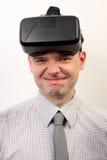 Ein lustiger Mann, der den Kopfhörer der virtuellen Realität Oculus-Risses VR, herum täuschend trägt Stockbild