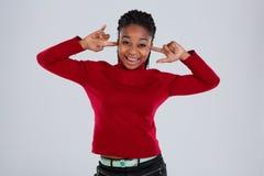 Ein lustiges afroes-amerikanisch Mädchen verzieht ein Gesicht Gesicht und setzt ihre Finger in ihre Ohren ein Lizenzfreie Stockfotografie