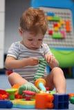 Ein lustiges Baby, das versucht, Socken zu kleiden Stockfotografie