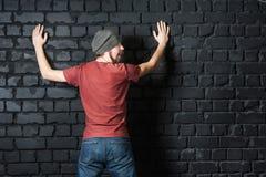 Ein lustiges Bild eines bärtigen Kerls, der durch die Polizei und den Glanz mit einer Taschenlampe gesucht wird Lizenzfreie Stockfotografie