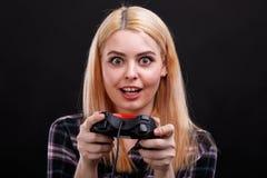 Ein lustiges junges Mädchen spielt faszinierend mit Steuerknüppel mit einem erschrockenen Blick Auf einem schwarzen Hintergrund lizenzfreie stockfotografie