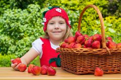Ein lustiges kleines Mädchen 4 Jahre alt mit einem Korb von Erdbeeren stockfotografie