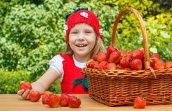 Ein lustiges kleines Mädchen 4 Jahre alt mit einem Korb von Erdbeeren Stockbilder