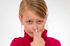 Ein Mädchen überwindt seine Furcht und benutzt das Nasenspray, das auf Weiß lokalisiert wird lizenzfreie stockfotos