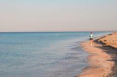Ein Mädchen auf dem Strand macht einen Morgenstoß entlang dem Meer sport stockfoto