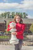Ein Mädchen auf einem großen Schachbrett mit einer Zahl stockfoto