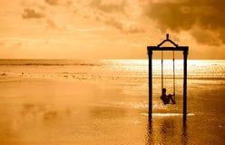 Ein Mädchen auf einem Schwingen über dem Meer bei Sonnenuntergang in Bali, Indonesien Lizenzfreie Stockfotos