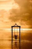 Ein Mädchen auf einem Schwingen über dem Meer bei Sonnenuntergang in Bali, Indonesien 3 Stockfoto