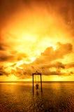 Ein Mädchen auf einem Schwingen über dem Meer bei Sonnenuntergang in Bali, Indonesien 4 Lizenzfreie Stockfotos