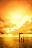 Ein Mädchen auf einem Schwingen über dem Meer bei Sonnenuntergang in Bali, Indonesien 5 Lizenzfreie Stockbilder