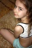 Ein Mädchen auf einem Teppich Lizenzfreie Stockfotos