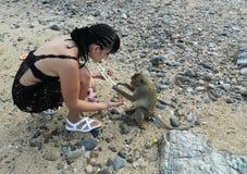 Ein Mädchen auf einer Insel, die mit einem wilden Affen spielt lizenzfreie stockbilder