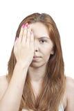 Ein Mädchen bedeckt ihr Gesicht mit seiner Hand Lizenzfreie Stockbilder