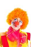Ein Mädchen, das als Clown gekleidet wird, schaut oben Stockbild