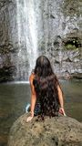 Ein Mädchen, das auf dem großen Felsen gegenüberstellt Wasserfälle sitzt Stockfotografie
