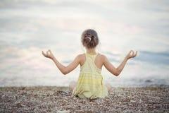 Ein Mädchen, das auf dem Strand meditiert Stockfotografie