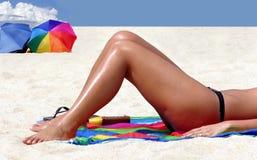 Ein Mädchen, das auf dem Strand sich bräunt Stockfoto