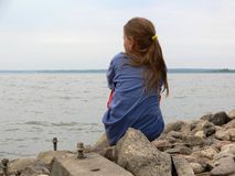 Ein Mädchen, das auf den Felsen durch den Strand sitzt Stockfotografie