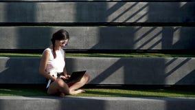 Ein Mädchen, das auf der Treppe sitzt und Laptop verwendet stock footage
