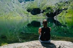 Ein Mädchen, das auf einem Felsen, eine großartige Ansicht des Berges betrachtend sitzt, der im See sich reflektiert lizenzfreies stockfoto