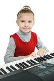 Ein Mädchen, das auf einer digitalen Tastatur spielt Stockbild
