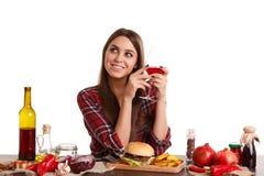 Ein Mädchen, das bei Tisch mit Lebensmittel sitzt und ein Glas mit Wein hält, oben lächelt und schaut Lokalisiert auf Weiß lizenzfreies stockfoto
