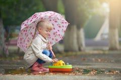 Ein Mädchen, das in der Pfütze mit dem Boot nach Regen spielt stockbild