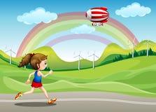 Ein Mädchen, das in die Straße und ein Luftschiff über ihr läuft Stockfotos